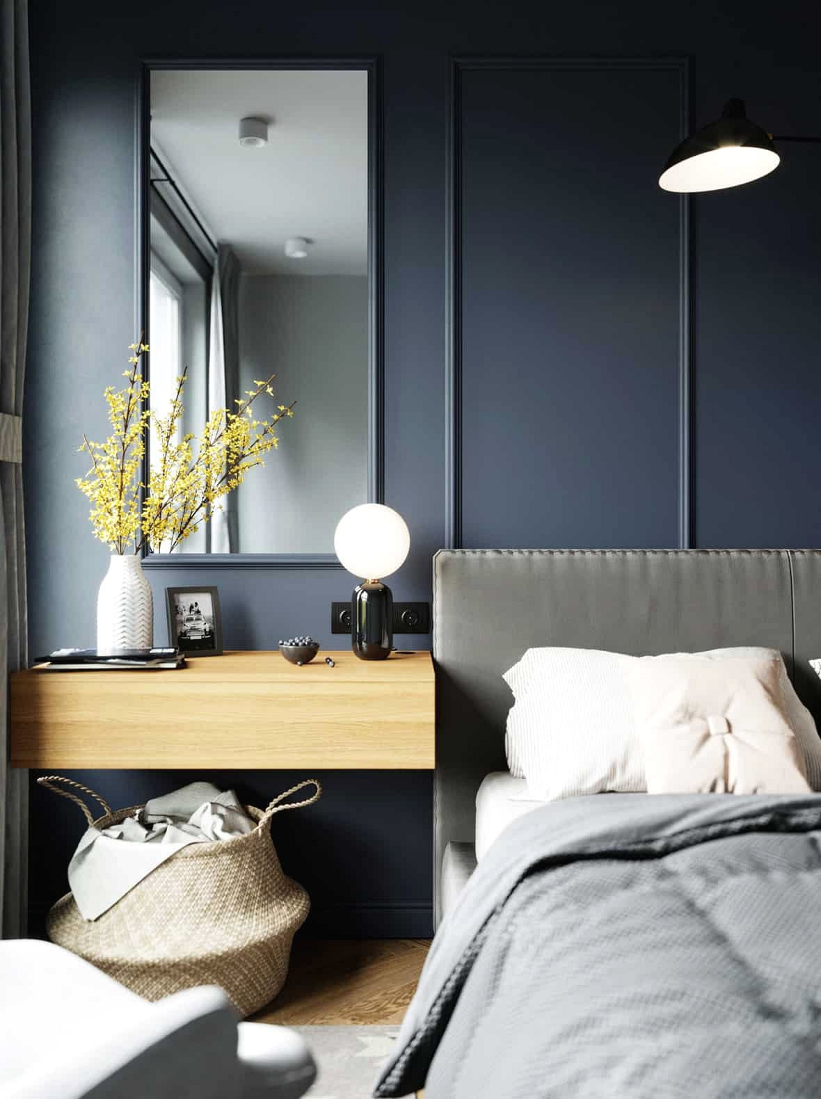 Trên bàn trang điểm treo tường, một chiếc bình trang trí hoa màu vàng tương phản đậm với bức tường màu xanh đằng sau nó.