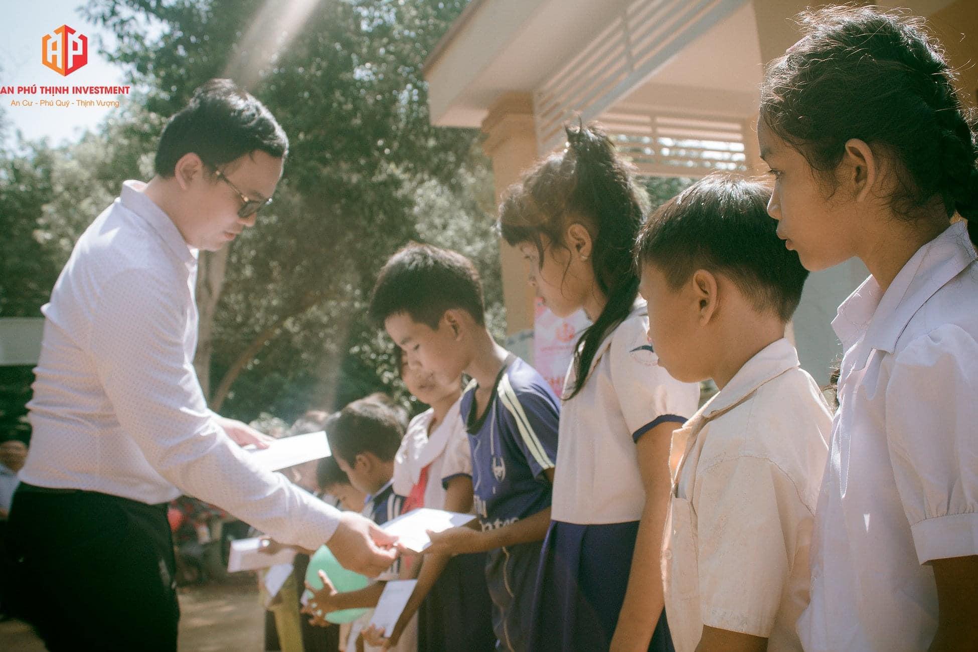 """Tổng Giám Đốc Công Ty Cổ Phần và Phát Triển Nhà Đông Á ông """"Đặng Hữu Lộc"""" đang trao học bổng cho các em"""